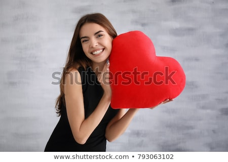 lovely woman with red heart shaped pillow stock photo © dolgachov