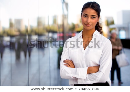 Portrait of beautiful mixed-race female executive standing in modern office with diverse business te Stock photo © wavebreak_media