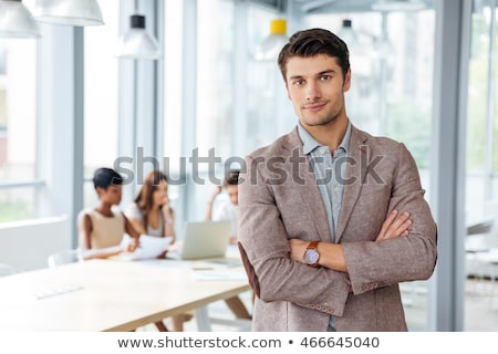 Stock photo: Smiling young businessman with folded arms