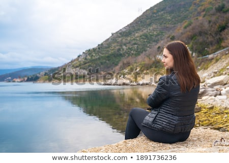 Beautiful young brunette woman against rocky shore or beach  Stock photo © master1305