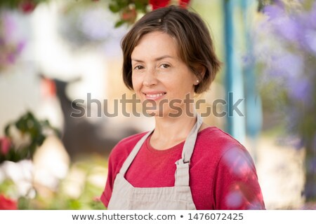 Young successful florist or sales clerk in apron and t-shirt looking at you Stock photo © pressmaster