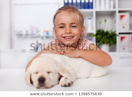 happy little girl holding her sleeping puppy dog at the veterina stock photo © ilona75