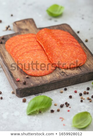 Spicy pepperoni salami with basil and pepper on wooden chopping board and light kitchen table backgr Stock photo © DenisMArt