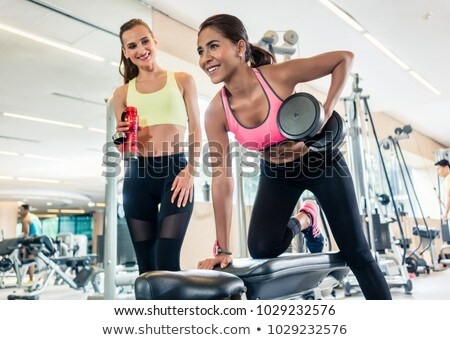 Powerful young woman smiling while rowing with one arm in a trendy health club Stock photo © Kzenon