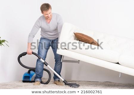Jonge aantrekkelijk man schoonmaken vacuüm tapijt Stockfoto © justinb