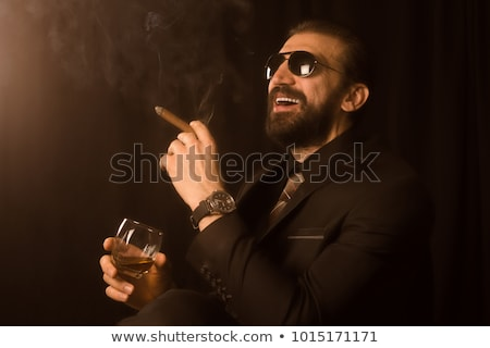 Businessman in a suit holds smoke Stock photo © cherezoff