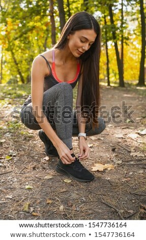 Pretty young fitness lady sitting and tie laces Stock photo © deandrobot