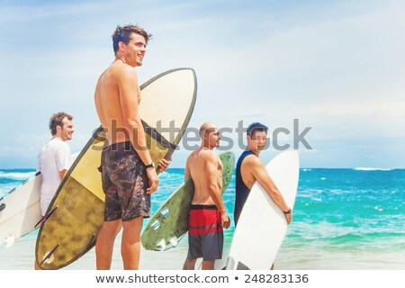 Four people in the water with surfboards Stock photo © IS2