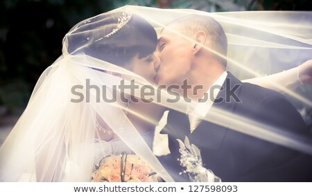 couple kisses and is covered with a bouquet Stock photo © ruslanshramko