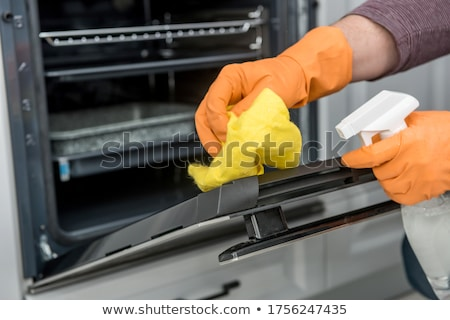Férfi gondnok takarítás sütő konyha közelkép Stock fotó © AndreyPopov