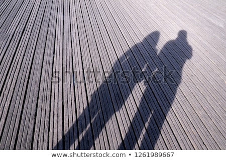 Young couple in love outdoors casting a lovely shadow on a woode Stock photo © lightpoet