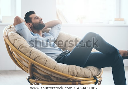young man relaxing on a chair stock photo © feedough