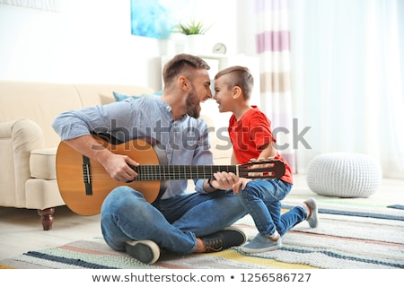 father and son playing guitar at home stock photo © zurijeta