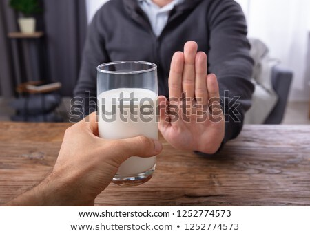 Man Refusing Glass Of Milk Offered By Person Stock photo © AndreyPopov