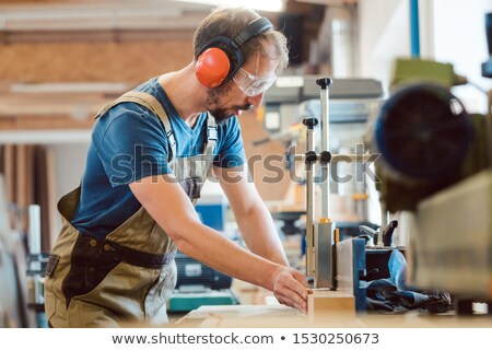 Absorbed carpenter at the milling machine working on wood Stock photo © Kzenon