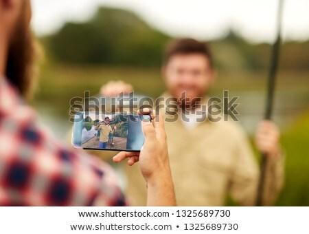 friend photographing fisherman by smartphone Stock photo © dolgachov