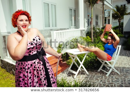 happy smiling pin up girl reading book outdoors stock photo © deandrobot