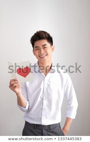 lezser · fiatalember · tart · lap · papír · mosolyog - stock fotó © szefei
