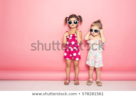Two cute little girls standing in jumpers and sun glasses on the terrace background in the studio. S Stock photo © ElenaBatkova