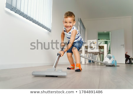 Boy using vacuum cleaner in living room at home Stock photo © wavebreak_media