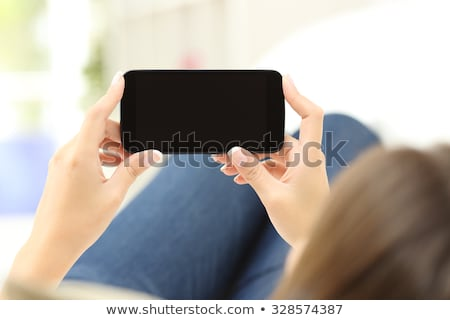 Happy restful girl lying on couch and looking at display of laptop on the floor Stock photo © pressmaster