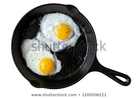 Frying eggs in a cast iron pan Stock photo © sumners
