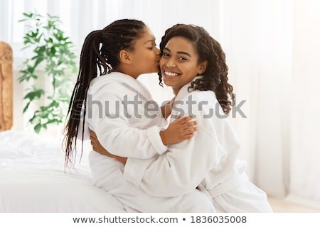 Happy daughter kissing mother while resting on bed Stock photo © wavebreak_media