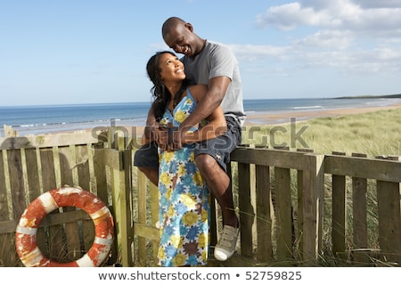 romantic young couple standing by wooden fence of beach hut amon stock photo © monkey_business