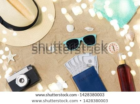 money in passport, shades and hat on beach sand Stock photo © dolgachov