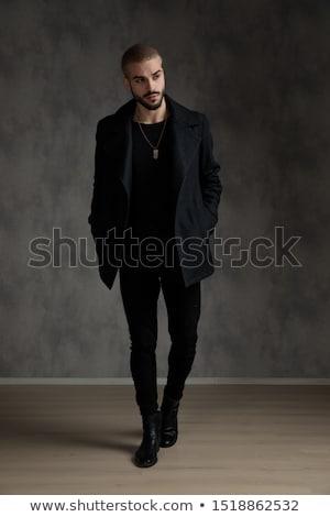 Attractive young blonde in black coat Stock photo © acidgrey