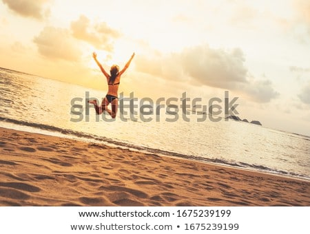 Fit woman in white bikini leaping on beach Stock photo © wavebreak_media