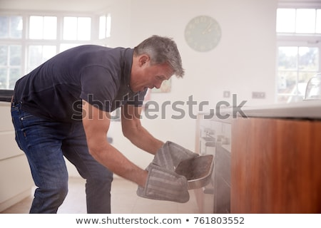 Hombre apertura horno humo joven Foto stock © AndreyPopov