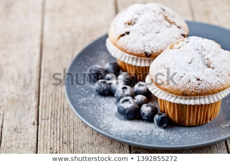 Two homemade fresh muffins with sugar powder and blueberries on  Stock photo © marylooo