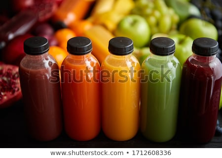Colorful bottles filled with fresh fruit and vegetable juice or smoothie Stock photo © dash