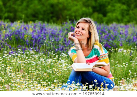Blonde girl reading the flowery meadow. Stock photo © justinb