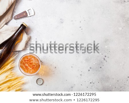 Glass bottles of craft lager beer with raw wheat and opener on s Stock photo © DenisMArt