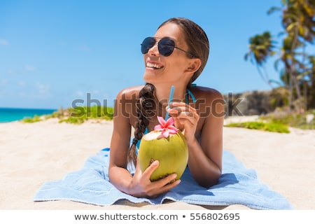 woman in bikini drinking the coconut water at beach stock photo © andreypopov