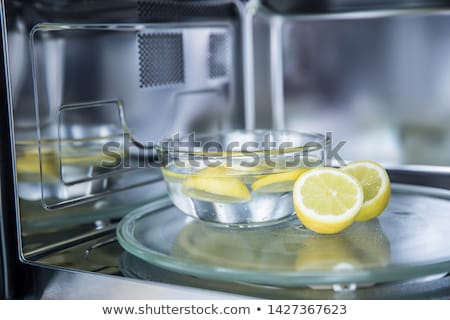 Woman Cleaning Microwave With Lemon Stock photo © AndreyPopov