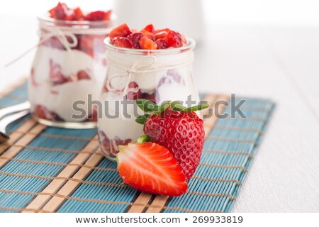Yogurt On A Spoon Over Yogurt In A Glass Bowl Foto stock © homydesign