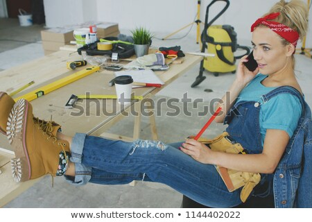 Relaxed female at workbench talking on smartphone  Stock photo © dash