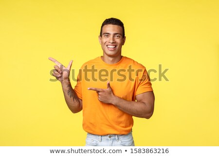 Cheerful modern man with tattooed arm, pointing left as promoting online store, invite guest join pa Stock photo © benzoix