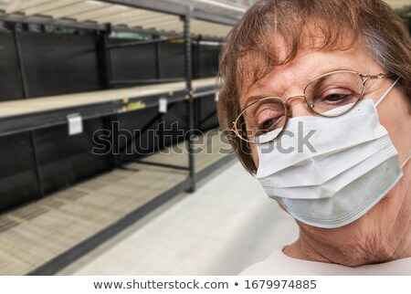 Senior Adult Woman In Medical Face Mask Walking Down Empty Aisle Stock photo © feverpitch