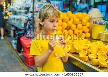 Little boy tourist drinks freshly squeezed orange juice on a walking street of Seoul. Fresh juice is Stock photo © galitskaya