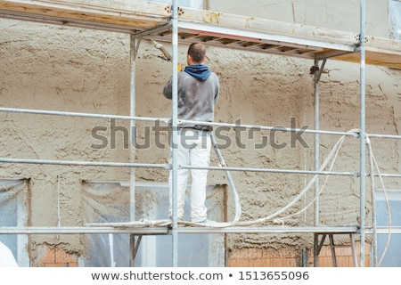 Worker plastering outer wall of newly built house Stock photo © Kzenon