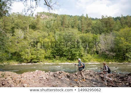 Backpackers with trekking sticks moving down river bank on summer day Stock photo © pressmaster