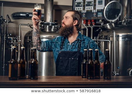 men drinking and testing craft beer at brewery Stock photo © dolgachov