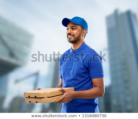 happy indian delivery man with pizza boxes in city stock photo © dolgachov