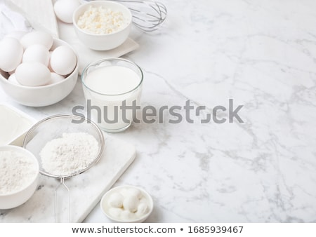 Fresh dairy products on white table background. Glass jar of milk, bowl of cottage cheese and baking Stock photo © DenisMArt