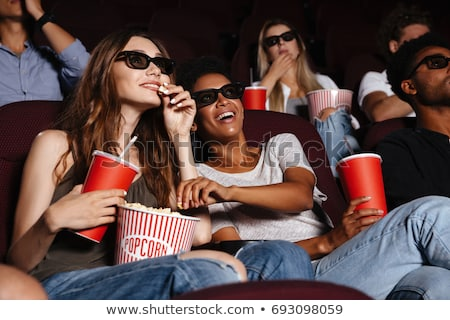 african woman eating popcorn at movie theater Stock photo © dolgachov