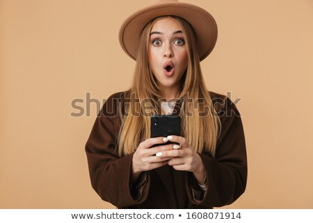 Image of young optimistic girl wearing hat wondering and holding Stock photo © deandrobot
